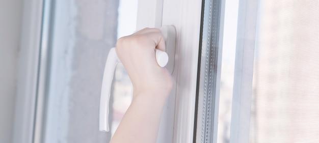 Little girl opens the window