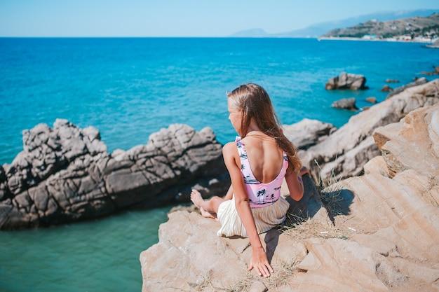 절벽 해변의 가장자리에 야외 어린 소녀