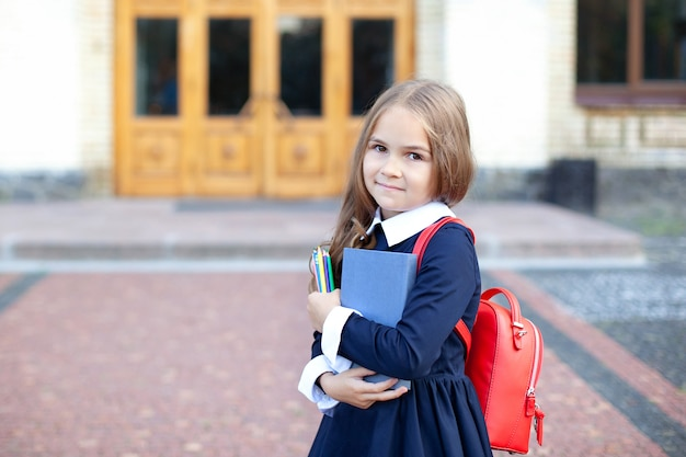 Маленькая девочка на открытом воздухе возле здания школы. школьница с книгой, карандашом и школьной сумкой.