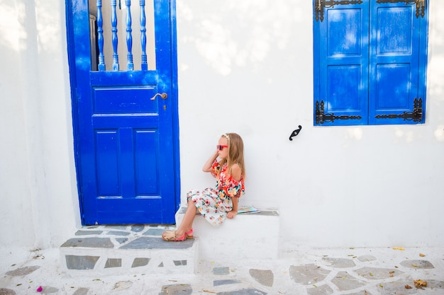 Little girl outdoors in old streets an mykonos. kid at street of typical greek traditional village with white walls and colorful doors on mykonos island, in greece