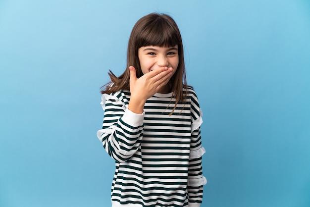 孤立した背景の上の少女幸せと笑顔の手で口を覆う