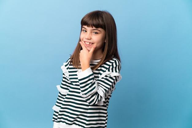 Маленькая девочка на изолированном фоне счастлива и улыбается