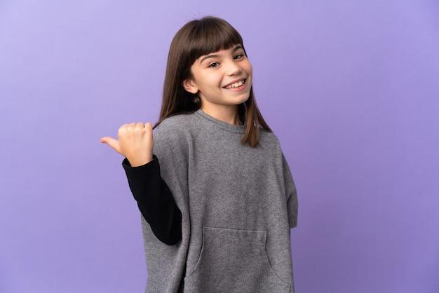 Маленькая девочка на изолированном фоне, указывая в сторону, чтобы представить продукт