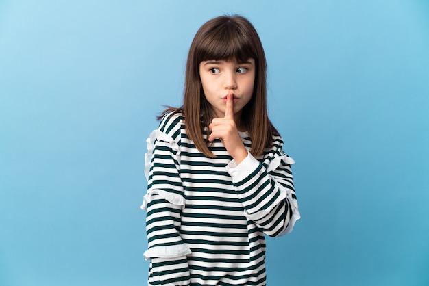 입에 손가락을 넣어 침묵 제스처의 기호를 보여주는 격리 된 배경 위에 어린 소녀