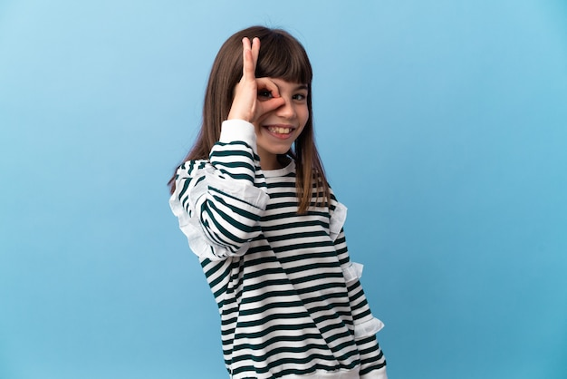 손가락으로 ok 사인을 보여주는 고립 된 배경 위에 어린 소녀