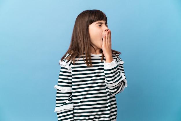 あくびと手で大きく開いた口を覆う孤立した背景の上の小さな女の子