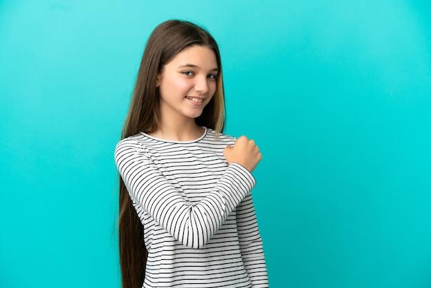 승리를 축하하는 고립된 파란색 배경 위에 어린 소녀