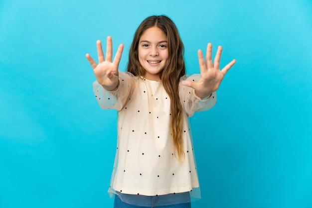 Маленькая девочка на изолированном синем фоне, считая девять пальцами
