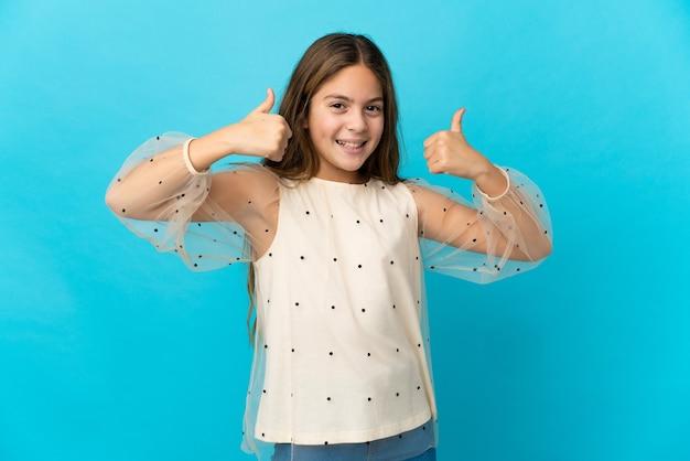 제스처를 엄지 손가락을주는 고립 된 파란색 배경 위에 어린 소녀