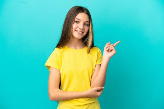 고립 된 파란색 배경 위에 어린 소녀 행복 하 고 가리키는