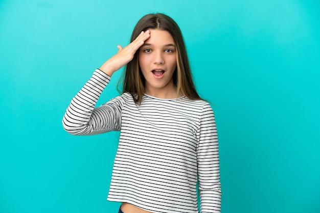 고립된 파란색 배경 위에 있는 어린 소녀는 무언가를 깨닫고 해결책을 의도하고 있습니다