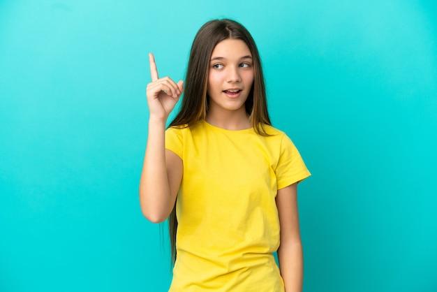 격리된 파란색 배경 위에 있는 어린 소녀가 손가락을 들어올리면서 솔루션을 실현하려고 합니다.
