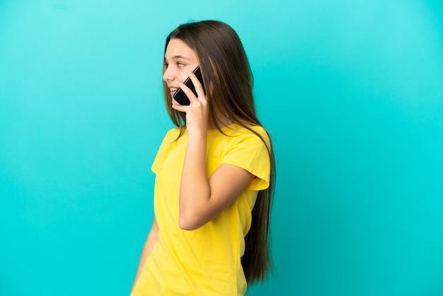 Маленькая девочка на изолированном синем фоне, разговаривая с кем-то по мобильному телефону
