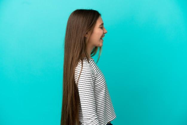 Маленькая девочка на изолированном синем фоне смеется в боковом положении