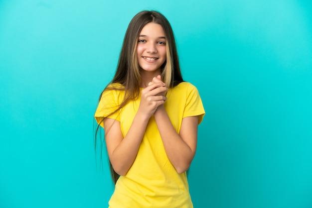 Маленькая девочка на изолированном синем фоне смеется