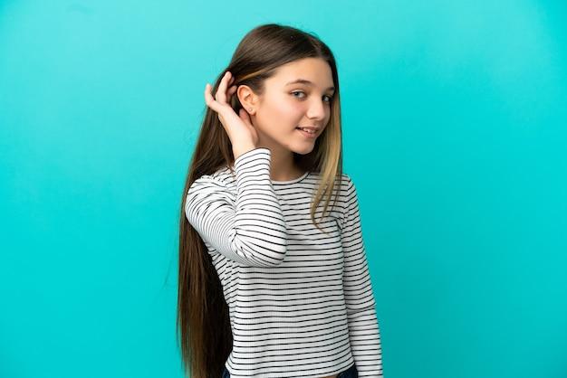 耳に手を置いて何かを聞いている孤立した青い背景の上の少女