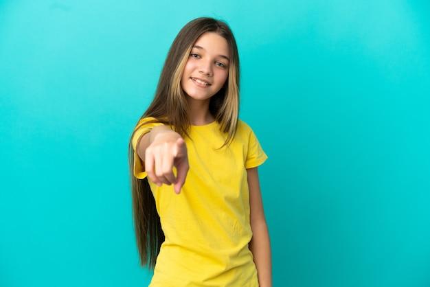 행복 한 표정으로 앞을 가리키는 고립 된 파란색 배경 위에 어린 소녀