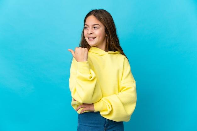 製品を提示する側を指している孤立した青い背景の上の少女