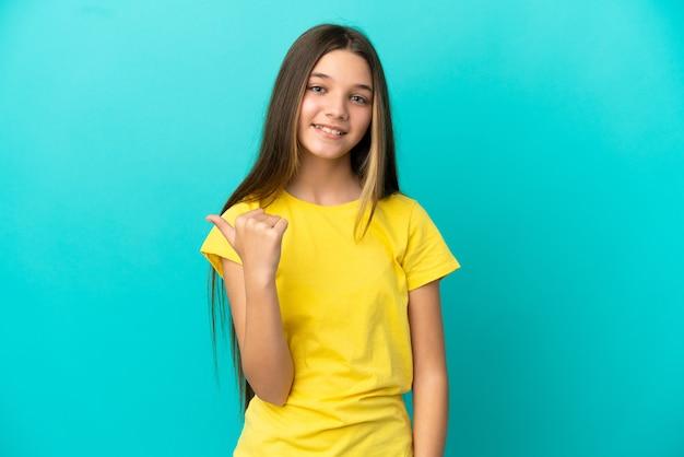 제품을 제시하기 위해 측면을 가리키는 고립된 파란색 배경 위에 어린 소녀