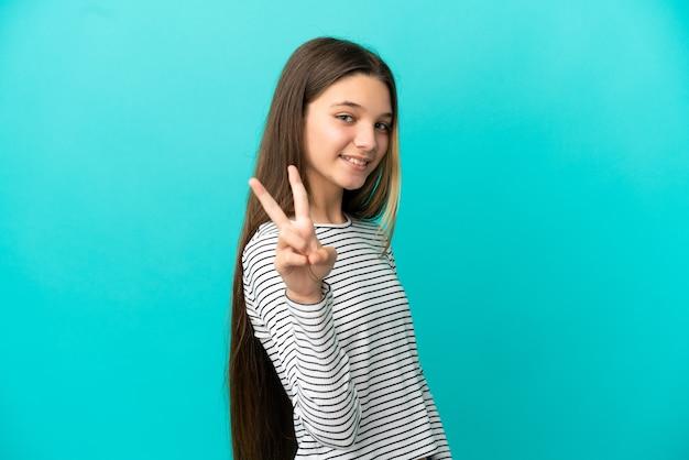 Маленькая девочка на изолированном синем фоне улыбается и показывает знак победы