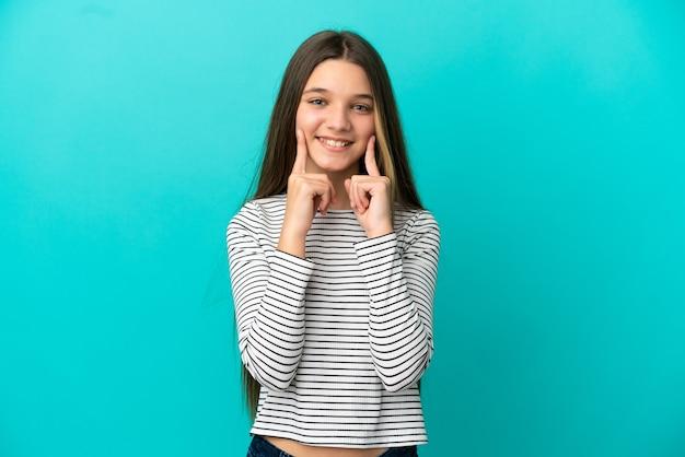 행복하고 즐거운 표정으로 웃고 있는 고립된 파란색 배경 위에 있는 어린 소녀