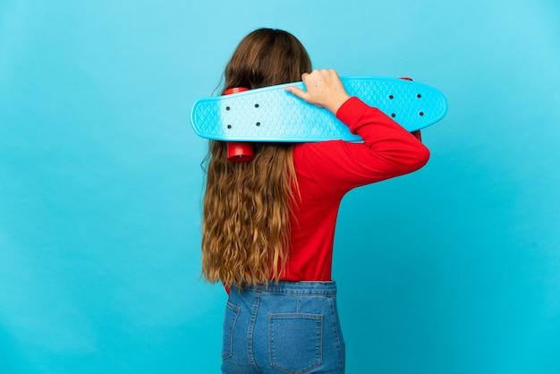 다시 위치에서 스케이트와 격리 된 파란색 배경 위에 어린 소녀