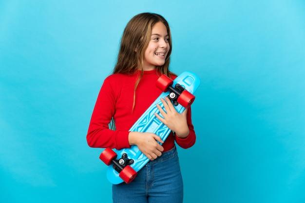 행복 한 표정으로 스케이트와 격리 된 파란색 배경 위에 어린 소녀