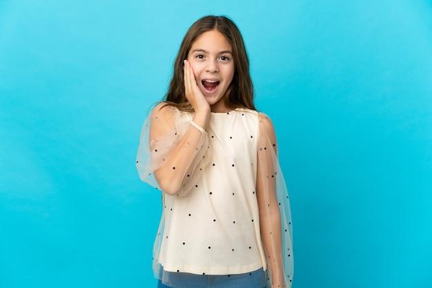 놀람과 충격 된 표정으로 격리 된 파란색 배경 위에 어린 소녀