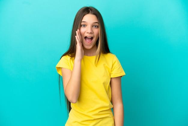 놀라움과 놀란 표정으로 고립된 파란색 배경 위에 있는 어린 소녀