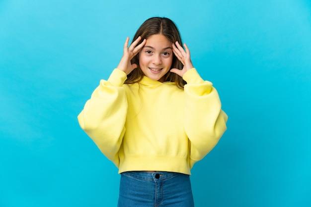 Маленькая девочка на изолированном синем фоне с выражением удивления
