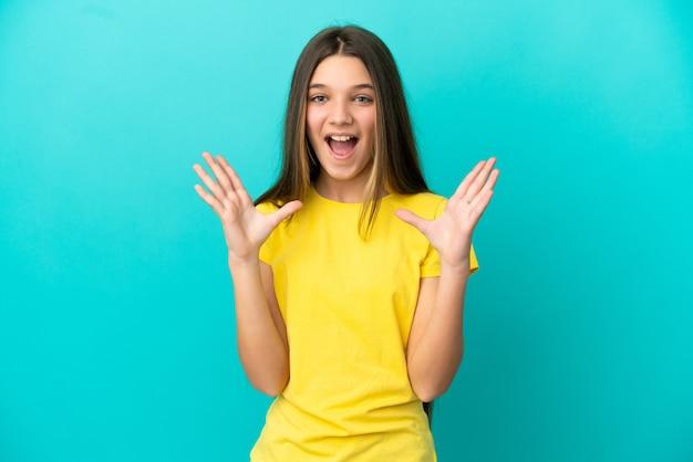 놀란 표정으로 고립된 파란색 배경 위에 어린 소녀
