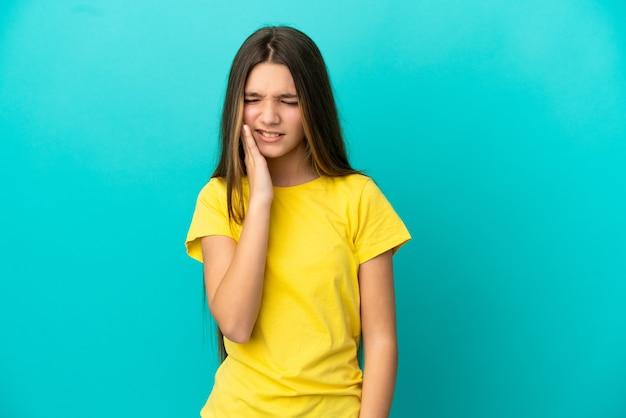 Маленькая девочка на изолированном синем фоне с зубной болью
