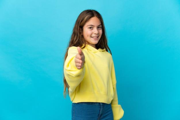 좋은 거래를 닫기 위해 악수하는 고립 된 파란색 위에 어린 소녀