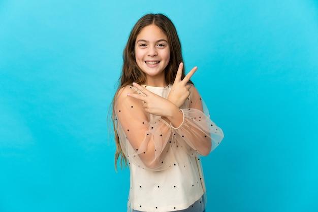 Маленькая девочка над изолированным синим улыбается и показывает знак победы