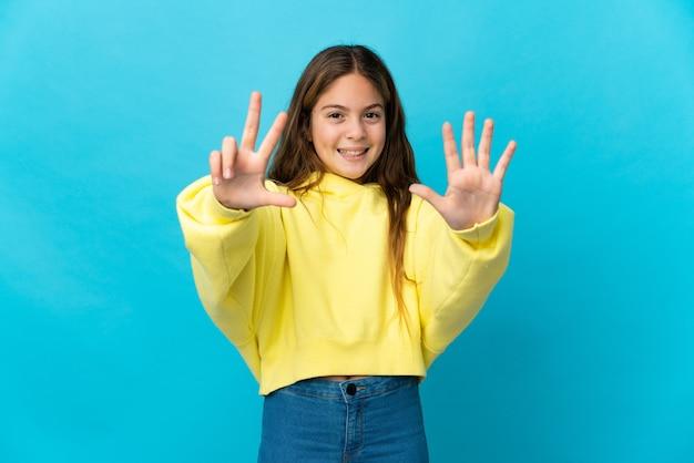 손가락으로 8 세 고립 된 파란색 벽 위에 어린 소녀