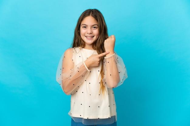 늦는 제스처를 만드는 격리 된 파란색 벽 위에 어린 소녀