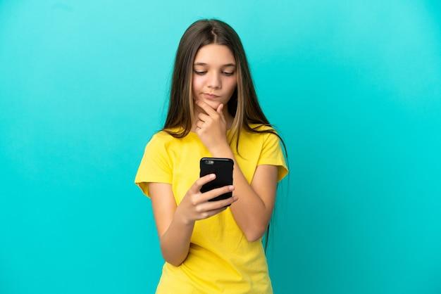 Маленькая девочка над изолированной синей стеной думает и отправляет сообщение