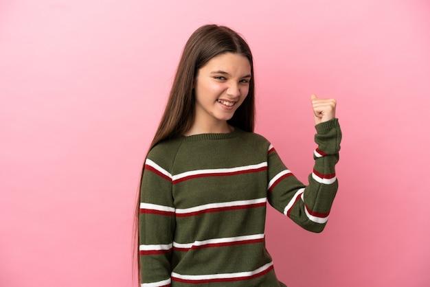 승리를 축하하는 고립된 분홍색 배경 위에 어린 소녀
