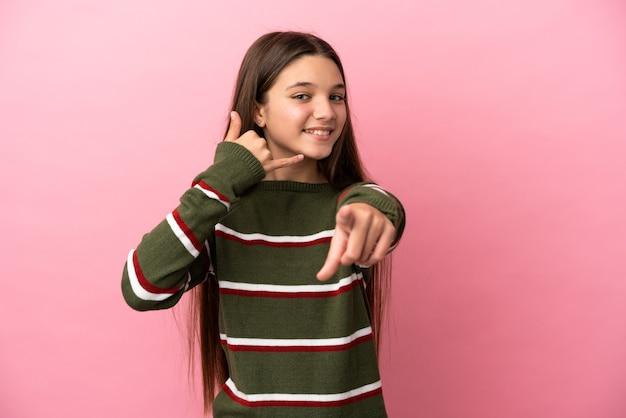 電話のジェスチャーをし、正面を指す孤立したピンクの背景上の少女