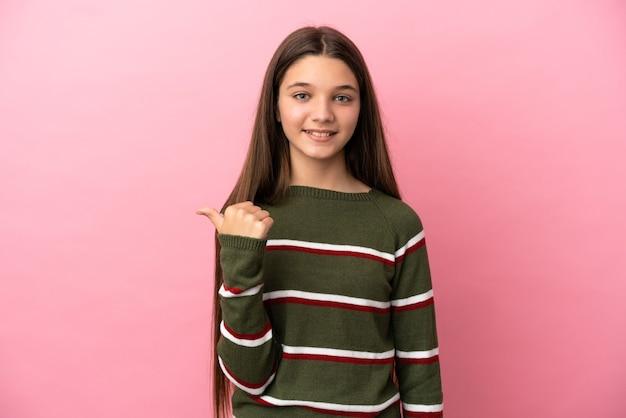 제품을 제시하기 위해 측면을 가리키는 격리된 분홍색 배경 위에 있는 어린 소녀