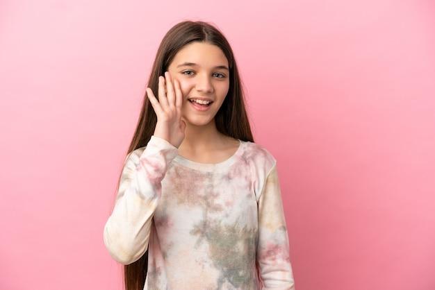 Маленькая девочка на изолированном розовом фоне кричит с широко открытым ртом