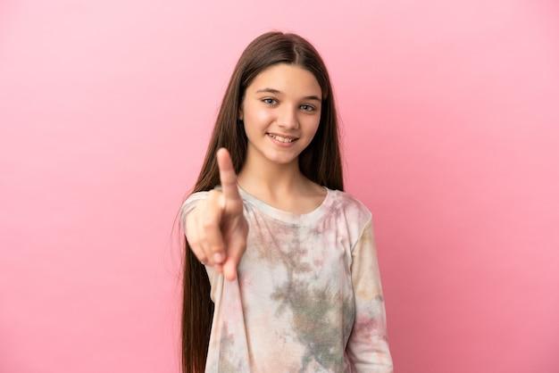 손가락을 보여주고 들어올리는 고립된 분홍색 배경 위에 있는 어린 소녀