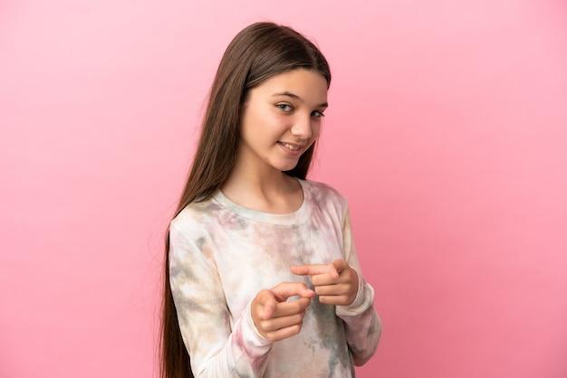 격리된 분홍색 배경 위에 있는 어린 소녀가 놀라 앞을 가리키고 있습니다.