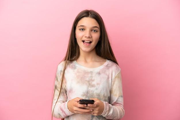 격리된 분홍색 배경 위에 있는 어린 소녀가 놀라서 메시지를 보냅니다.