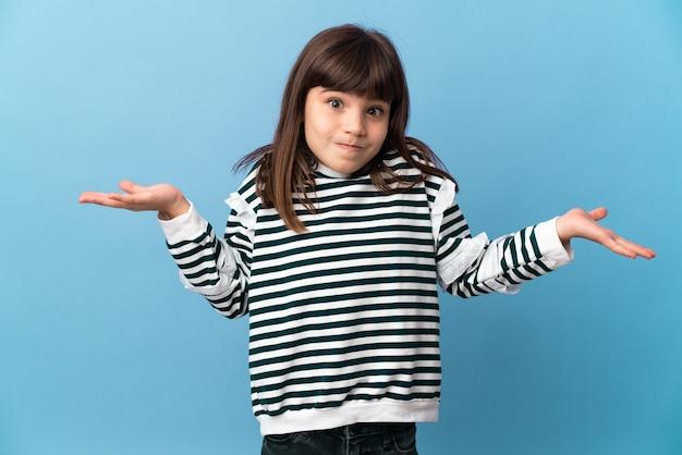 Маленькая девочка над изолированной стеной, сомневаясь, поднимая руки