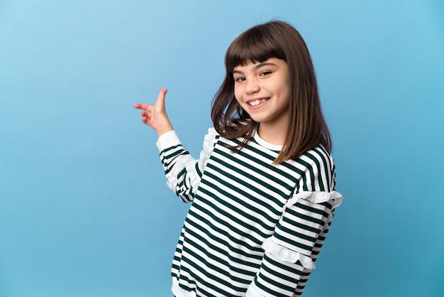 Маленькая девочка над изолированной стеной, указывая назад