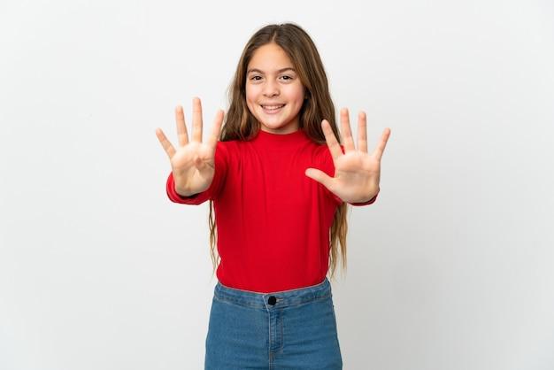 Маленькая девочка на изолированном белом фоне, считая девять пальцами