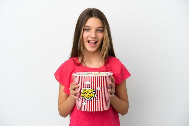 ポップコーンの大きなバケツを保持している孤立した白い背景の上の少女