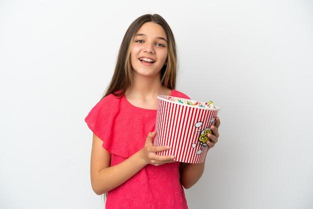 Маленькая девочка на изолированном белом фоне держит большое ведро попкорна