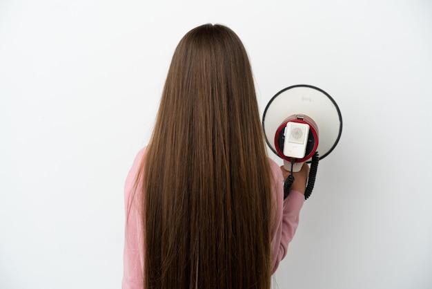 Маленькая девочка на изолированном белом фоне, держа мегафон и в задней позиции